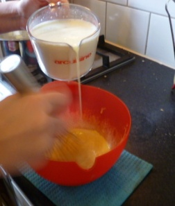 Adding milk to eggs to make custard, slowly at first